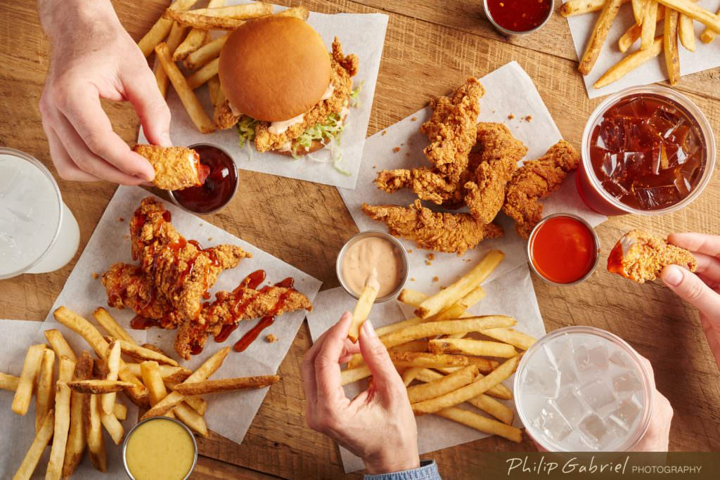 Food Overhead Family Meal Chicken Fries and Dips Sauces with Hands Styled Photographed by Philip Gabriel Photography